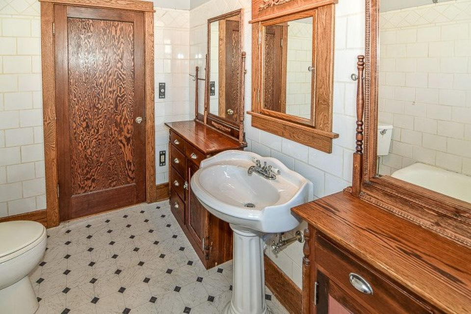 white bathroom with wooden door